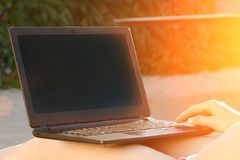 Open laptop on female lap. Outdoors, sunlight.  Stock Images