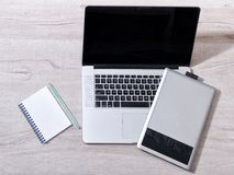 Open the laptop, graphics tablet and notepad with pensil on a light table, top view Stock Photos