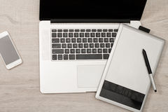 Open the laptop, graphics tablet and smart phone on a light table, top view Royalty Free Stock Photos