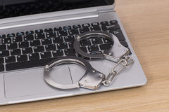 Open laptop with locked handcuffs on the keyboard Stock Images