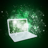 Open laptop with magic light and falling stars Royalty Free Stock Photos