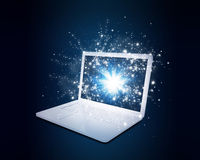 Open laptop with magic light and falling stars Stock Images