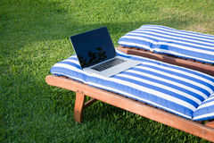 Open laptop on mat deckchair Royalty Free Stock Images