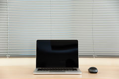 Open laptop with mouse and blind Royalty Free Stock Photo