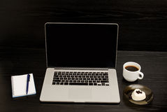 Open the laptop, mug of coffee, notepad and dessert on a black background Stock Photo