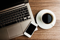 Open laptop with phone and cup of coffee Royalty Free Stock Images