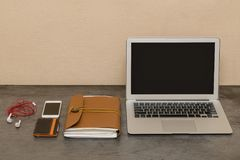 Open laptop, smartphone, wallet, headphones and a leather notebo. Ok. Workplace Stock Images