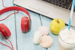 Open laptop with white Cup of coffee, marshmallows and red headphones. Open laptop with white Cup of coffee, marshmallows and red headphones Royalty Free Stock Photo