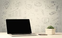 Urban sales graphs and laptop on desk. An open laptop on a white office desk with flower, coffee, books in front of wall background full of financial business Royalty Free Stock Images