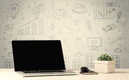 Urban sales graphs and laptop on desk. An open laptop on a white office desk with flower, coffee, books in front of wall background full of financial business Stock Images