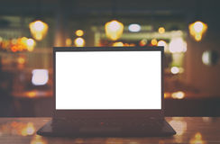 open laptop with white screen on wooden table in front of abstract blurred restaurant lights background. Stock Image