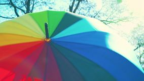 An open large umbrella of rainbow color turns, a colorful umbrella rotates in an open view stock video