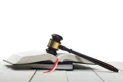 Open law book with wooden judges gavel on table in Royalty Free Stock Image