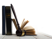 Open law book with wooden judges gavel on table in Royalty Free Stock Images
