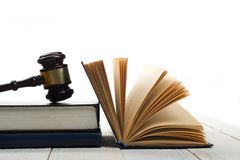 Open law book with wooden judges gavel on table in a courtroom Stock Images