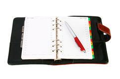 Open leather office organizer with a red pen. Open blank leather office organizer with a red pen on white Royalty Free Stock Photo
