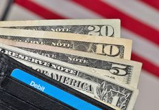 US dollars in wallet with US flag background. Open leather wallet displaying US dollars and a nondescript debit card with an American flag in the background Royalty Free Stock Photo