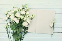 Open leeg notitieboekje en boeket van witte bloemeneustoma op blauwe rustieke lijst van hierboven Vrouwen werkend bureau Vlak leg stock foto