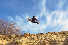Open-leg jump from sand Royalty Free Stock Image