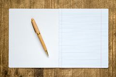 Open lined exercise book with a pen. Open white lined exercise book with a pen on the wooden table top Stock Photo