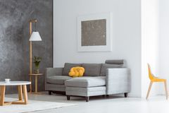 Open living room with furniture. Canary yellow color accent in simple open living room interior with gray couch, modern wooden furniture and abstract painting on Royalty Free Stock Photography