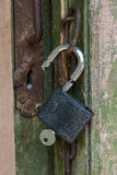 Open lock with a key hanging on an old door Royalty Free Stock Image