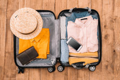 Open luggage full of clothes, document and smartphone on wooden floor, Summer travel concept Royalty Free Stock Photo