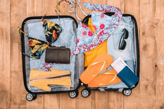Open luggage full of woman`s clothes and other essential vacation items. Ready to summer vacation Stock Photo