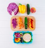 Open lunch box neat ingredients. Open lunch box with sandwich, vegetables, egg, fresh berries on the white wooden background. Top view, flat lay stock photos