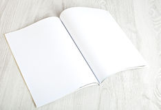 Open magazine with blank pages. On white table stock photography