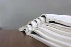 Open magazines lie on top of each other on a brown table, documents are stacked close-up.  royalty free stock image