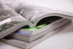 Open magazines. On white table Stock Image