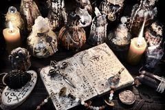 Open magic book with ancient symbols, witch bottles and black candles stock images