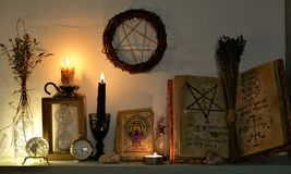 Open magic book with spells, tarot cards, crystals, candles and pentagram stock photos