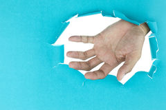 Open male hand through blue paper on white background. Stock Photo