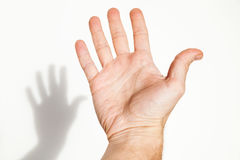 Open male hand over white wall. Background with soft shadow, closeup photo with selective focus Royalty Free Stock Images