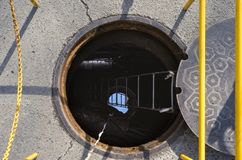 An open manhole on a city street royalty free stock images