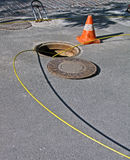 Open manhole with yellow optic cables, Royalty Free Stock Photo