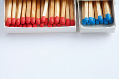Open matchstick boxes. Red, blue heads on white paper background. Macro view, soft focus Stock Photography