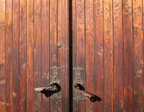 Open me !. Old wooden door with a wonderful colour gradient as result to long time exposure to the sun light. The lock are made from old copper (bronze) sheets Royalty Free Stock Photography