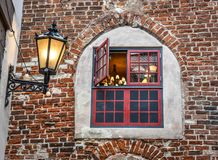 Open medieval wooden decorative window in an old brick home royalty free stock photo