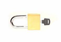 Open messingsslot met een sleutel die op wit wordt geïsoleerd stock afbeelding