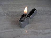 Open metaalaansteker met vlam op zwarte achtergrond stock afbeelding