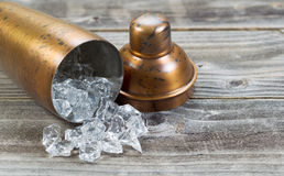 Open Metal Drink Mixer on its side with ice flowing out on to wo Stock Images