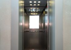 Open metal elevator doors. With a handrail and a mirror inside Stock Images