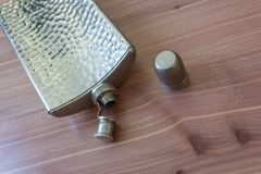 Open metal flask on wood background, drinking alcoholism addiction concept. Copy space, horizontal aspect Stock Images