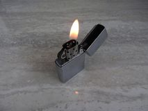 Open metal lighter with flame on black background stock image