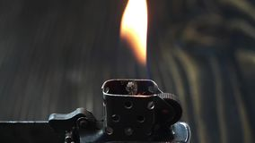 Open metal lighter with flame on dark background. Open metal lighter  with flame on dark background, close up stock video