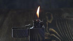 Open metal lighter with flame on dark background. Open metal lighter  with flame on dark background, close up stock footage