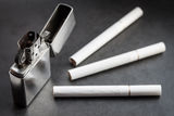 Open metal lighter and three cigarettes. Stock Image